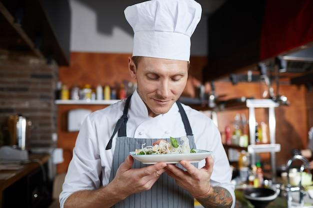 Stolzer koch, der gericht präsentiert