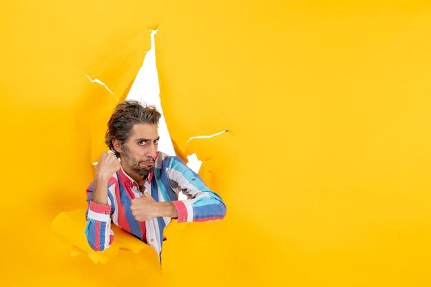 Stolzer und ehrgeiziger junger mann, der durch ein zerrissenes loch in gelbem papier für die kamera posiert