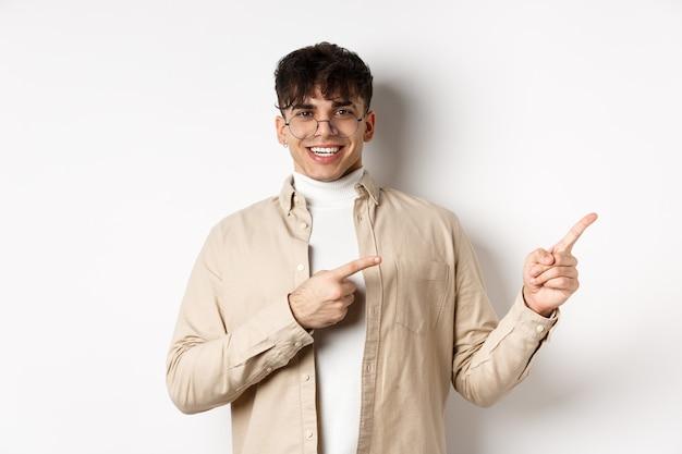 Stolzer und glücklicher junger mann mit brille, der logo zeigt, mit den fingern auf die obere rechte ecke zeigt und lächelt, auf weißem hintergrund stehend