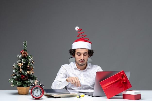 Stolzer zufriedener junger geschäftsmann mit lustigem weihnachtsmannhut im büro auf dunklem hintergrund