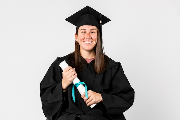 Stolzes mädchen in einem abschlusskleid, das ihr diplom hält