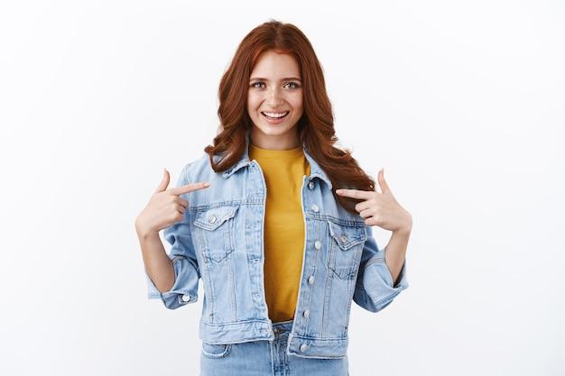 Stolzes und selbstbewusstes, motiviertes süßes ingwermädchen mit sommersprossen in jeansjacke, das sich selbst zeigt und prahlerisch lächelt, sich geehrt und selbstbewusst fühlt, hilfe vorschlagen, ziel erreichen, weiße wand