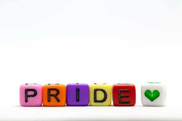 Stolzes wort geschrieben auf verschiedenen regenbogenwürfeln lokalisiert auf weißem hintergrund, mit buntem symbol des herzens lgbt konzept