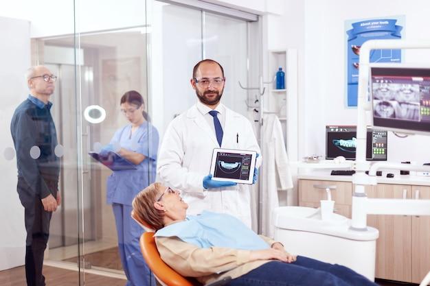 Stomatolog, der röntgenaufnahme einer älteren frau hält, die auf einem orangefarbenen stuhl im zahnarztkabinett sitzt. medizinischer zahnpfleger, der patientenradiographie auf tablet-pc in der nähe des aufstehenden patienten hält.