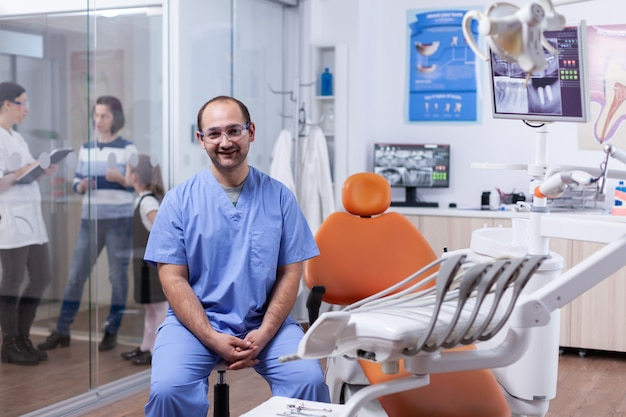 Stomatolog in professioanl zahnklinik lächelnd in uniform mit blick auf die kamera. zahnarztdoktor, der mit mutter und kind über zahnbehandlung diskutiert.