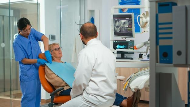 Stomatologe, der auf einen digitalen bildschirm zeigt und einer älteren frau das röntgenbild erklärt. arzt und krankenschwester arbeiten in einer modernen stomatologischen klinik zusammen, untersuchen, zeigen röntgenaufnahmen der zähne auf dem monitor