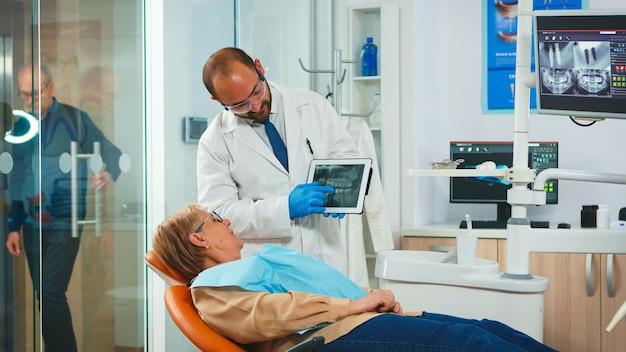 Stomatologe, der den röntgenstrahl des zahns mit einem älteren patienten überprüft, der die behandlung erklärt. zahnarzt, der der zahnmedizinischen radiographie der alten frau mit tablet, arzt und krankenschwester zeigt, die in der modernen klinik zusammenarbeiten.