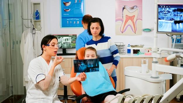 Stomatologe, der die zahnbehandlung erklärt und die röntgenaufnahme auf betroffene zähne zeigt, während der assistent sterilisierte werkzeuge für die operation vorbereitet. arzt und krankenschwester, die in der stomatologischen abteilung arbeiten