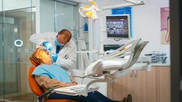 Stomatologe, der eine untersuchung durchführt und die zähne mit zahnärztlichen werkzeugen pflegt. kieferorthopäde, die mit einer frau spricht, die auf einem stomatologischen stuhl sitzt, während sich die krankenschwester auf die operation in der modernen klinik vorbereitet
