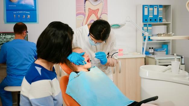 Stomatologe, der sterilisierte zahnwerkzeuge hält, die mit kleinem patienten vor stomatologischer intervention sprechen. krankenschwester und arzt tragen masken, die die zähne des auf dem stuhl liegenden kindes mit offenem mund reinigen