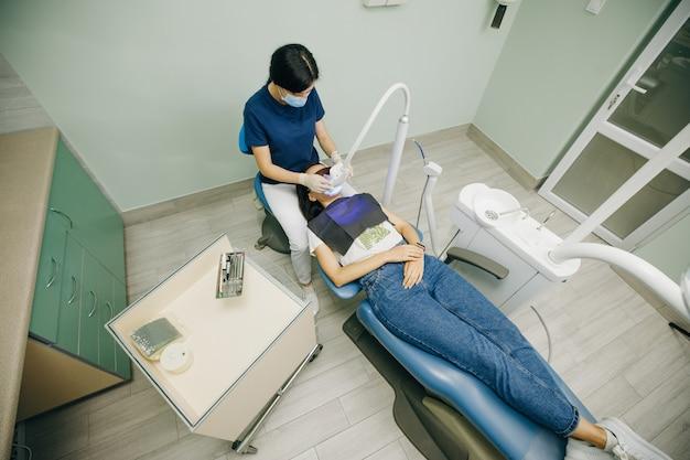 Stomatologe, der zähne für patienten in einer klinik aufhellt