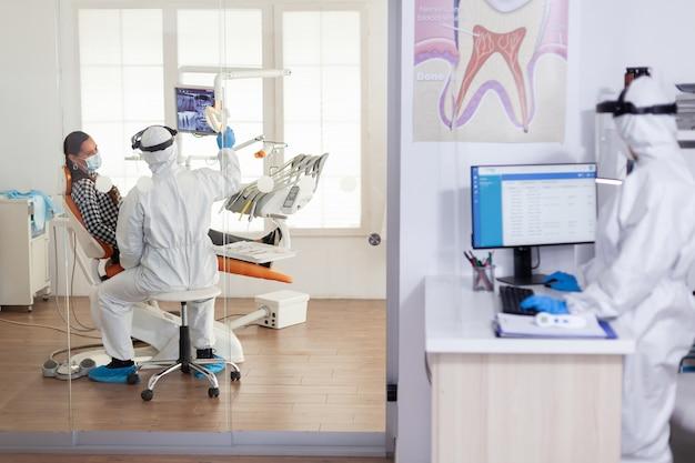 Stomatologe im schutzanzug bittet um zahnröntgenuntersuchung des patienten bei der untersuchung von zahnproblemen während der coronavirus-pandemie in einer modernen klinik