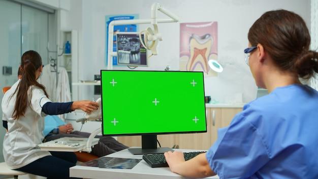 Stomatologenkrankenschwester, die auf die greenscreen-tablette schaut, während der fachzahnarzt patienten mit zahnschmerzen untersucht, die auf einem stomatologischen stuhl sitzen. frau mit monitor mit chroma-key izolated pc-key moc
