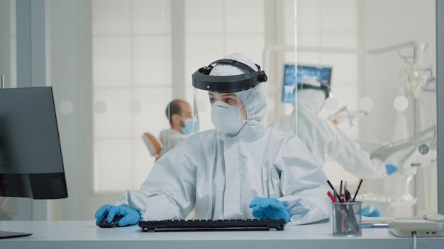 Stomatologie-assistent, der am schreibtisch mit computer sitzt
