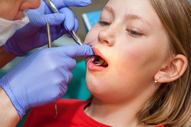 Stomatologie untersucht zähne für ein kind, mädchen auf einem empfang für stomatologie