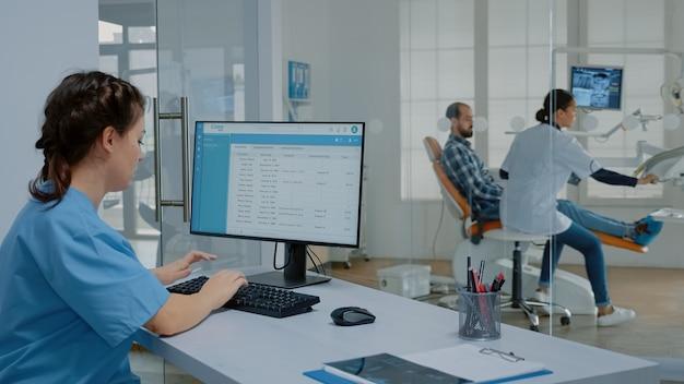Stomatologiekrankenschwester sitzt am schreibtisch und arbeitet am computer