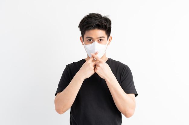 Stop civid-19, asiatischer mann mit gesichtsmaske zeigt stop-hand-geste für den ausbruch des corona-virus