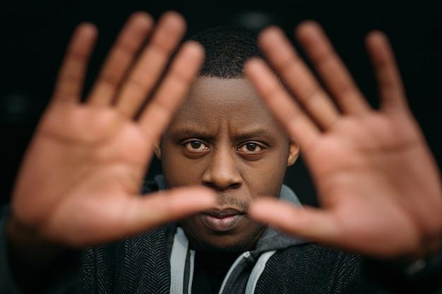 Stopp-geste. schwarzer mann im selektiven fokus. wütender afroamerikaner, gesichtsausdruck, nicht schuldiger kerl auf dunklem hintergrund, emotionales foto, schutzkonzept