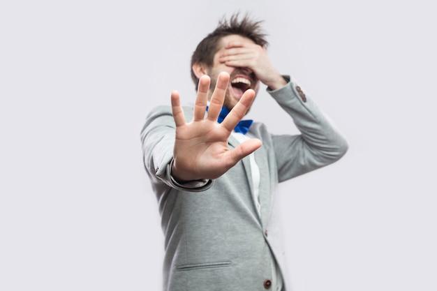 Stopp, ich will das nicht sehen. porträt eines schockierten oder verängstigten jungen bärtigen mannes im lässigen grauen anzug, der mit geschlossenen augen steht und mit der hand blockiert. indoor-studioaufnahme, isoliert auf hellgrauem hintergrund.