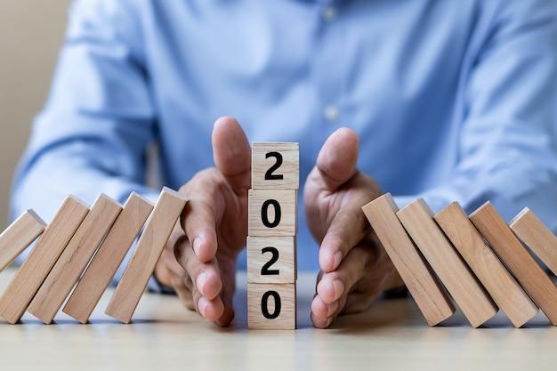 Stoppen des fallens von 2020 holzklötzen. geschäft, risikomanagement