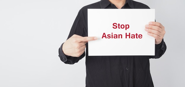 Stoppen sie asiatischen hass in roter farbe, schreiben sie in weißes brettpapier. asiatischer mann trägt schwarzes hemd, das papier auf weißem hintergrund hält.