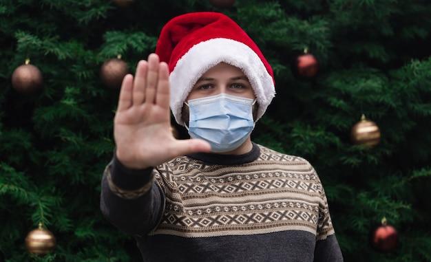 Stoppen sie corona weihnachten. schließen sie herauf porträt des mannes, der einen weihnachtsmannhut, weihnachtspullover und medizinische maske mit emotion trägt. vor dem hintergrund eines weihnachtsbaumes. coronavirus pandemie