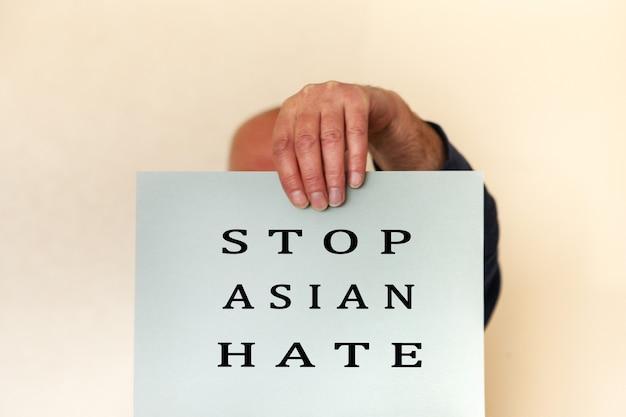 Stoppen sie das asiatische hasskonzept. männerhand, die kartenpapierblatt mit wort stoppt asiatischen hass für plakat der kampagne hält