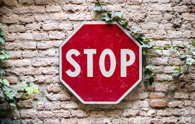 Stoppen sie das verkehrsschild, das zur backsteinmauer angebracht wird