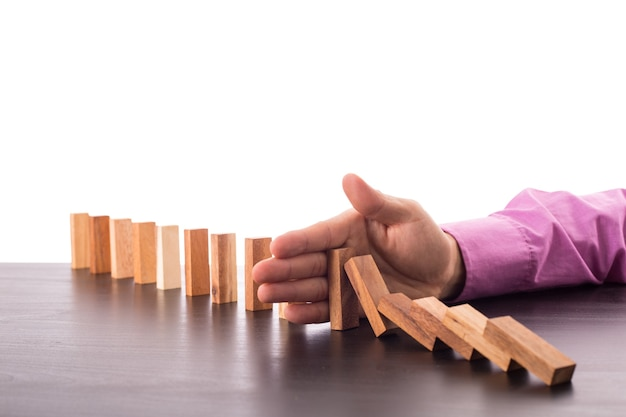 Stoppen sie den domino-risikoeffekt, geschäftsmann, der die hand für die managementlösung verwendet.