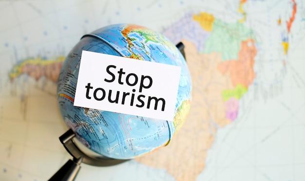 Stoppen sie den tourismus aufgrund der krise und pandemie, der beendigung von flügen und touren für reisen. text in einer hand auf dem hintergrund der karte von amerika