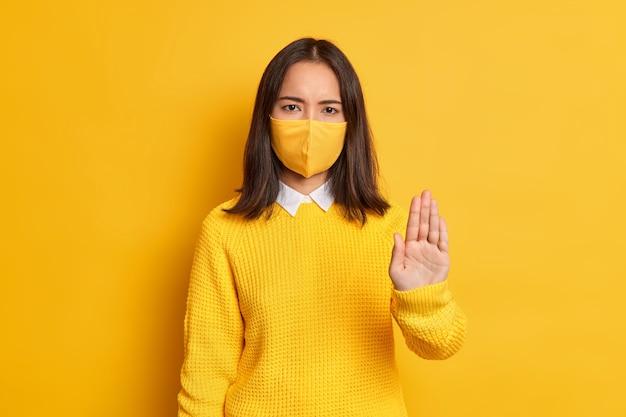 Stoppen sie den virus. ernsthafte verärgerte asiatische frau hält handfläche in stopp-geste nach vorne gezogen, trägt schutzmaske als vorbeugung gegen coronavirus