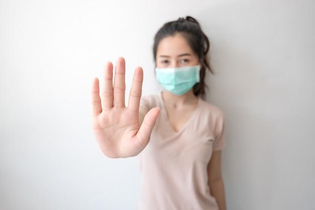 Stoppen sie die infektion! gesunde frau, die geste zeigt