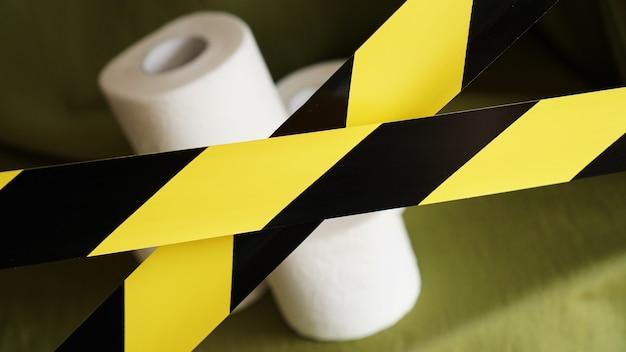 Stoppen sie die panik - coronavirus. toilettenpapierrollen hinter dem gelben klebeband