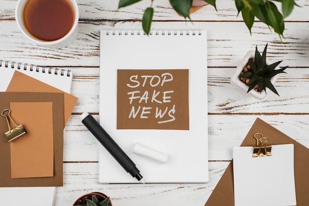 Stoppen sie gefälschtes nachrichtenkonzept mit schreibtisch