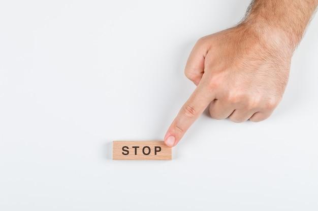 Stoppwortkonzept mit holzblöcken auf draufsicht des weißen hintergrunds. mit der hand hält es. horizontales bild