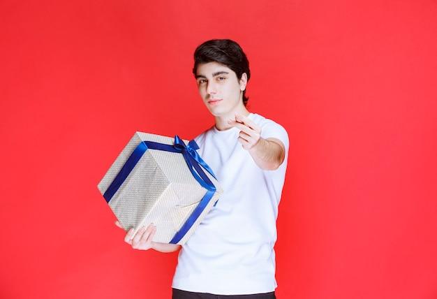Storeman hält eine weiße geschenkbox und bittet um zahlung