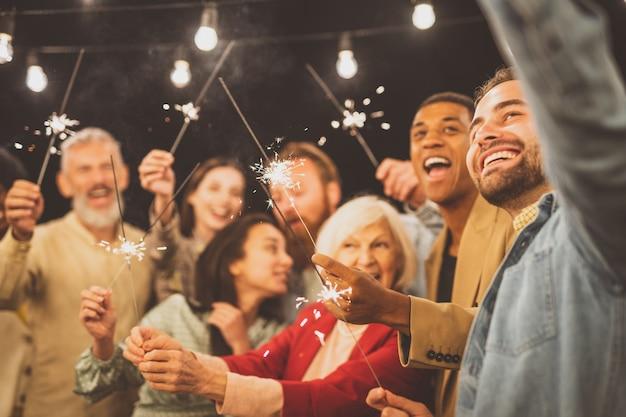 Storytelling-aufnahmen einer multiethnischen gruppe von menschen, die auf einem dach speisen. familie und freunde machen ein wiedersehen zu hause