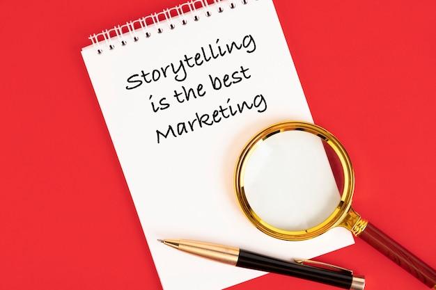 Storytelling ist das beste marketing, text, geschäftsphrase, motivation, geschrieben in einem weißen notizbuch auf rotem hintergrund.