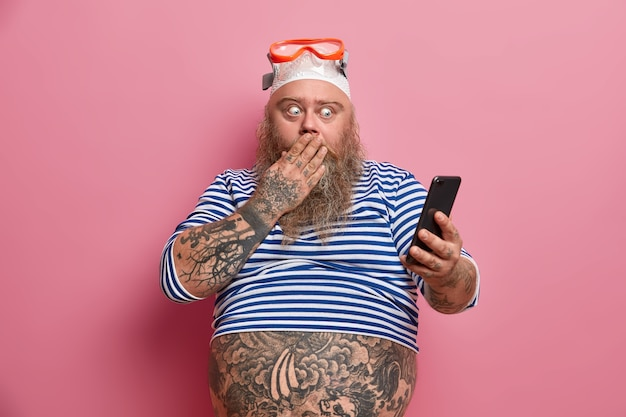 Stout schockiert bärtigen mann bedeckt mund und starrt auf smartphone, liest etwas erstaunliches, gekleidet in matrosenhemd, schwimmbrille, hat bauch tätowiert