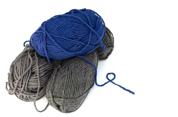 Stränge der wolle nahaufnahme auf weißem hintergrund, blaue und graue wolle isoliert