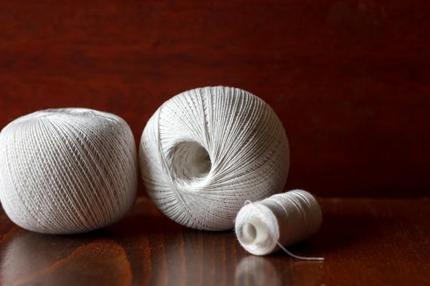 Stränge des weißen fadens auf dem tisch liegend für das stricken und die näharbeit.