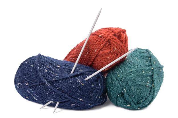 Stränge von farbigen garnen und stricknadeln lokalisiert auf weißem hintergrund.