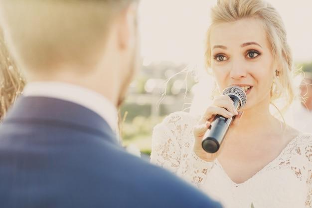 Strahlen der abendsonne machen einen heiligenschein um die braut, während sie ihrem bräutigam den eid schwört