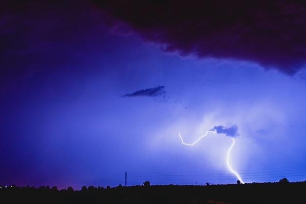 Strahlen in einem nachtsturm mit licht und wolken.