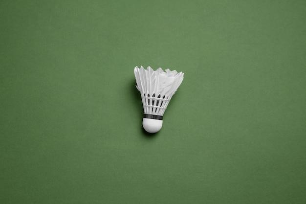 Strahlend weißer federball. professionelle sportausrüstung isoliert auf grüner oberfläche. konzept von sport, aktivität, bewegung, gesunde lebensweise, wohlbefinden. moderne farben.
