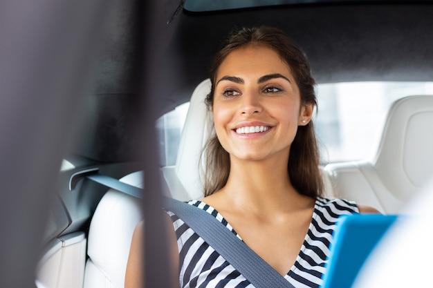 Strahlende geschäftsfrau. strahlende geschäftsfrau mit tablet lächelnd beim sitzen im auto