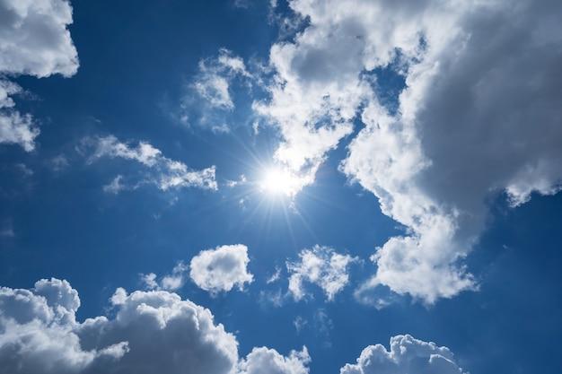 Strahlende sonne am klaren blauen himmel mit lens flare des sonnenlichts am himmelshintergrund helle sonne am blauen himmel konzept natur und umwelt hintergrund.