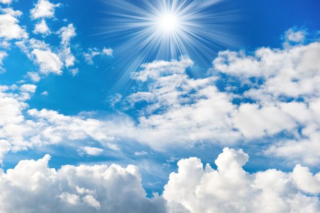 Strahlende sonne und strahlen am blauen himmel mit schönen weißen wolken