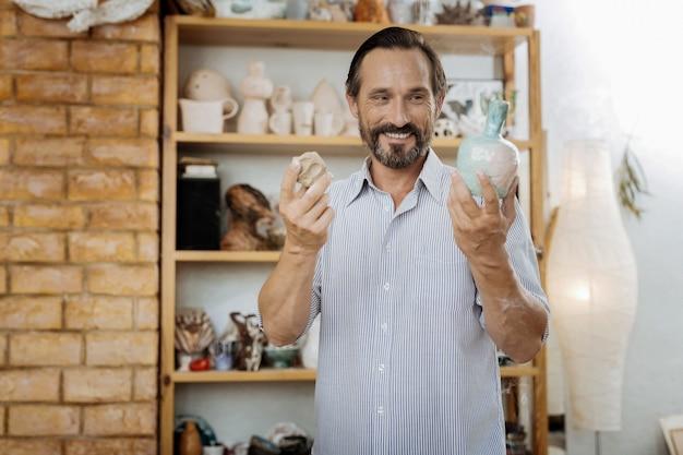 Strahlender mann. strahlend inspirierter mann, der hart in seinem neuen modernen arbeitszimmer arbeitet und vasen herstellt