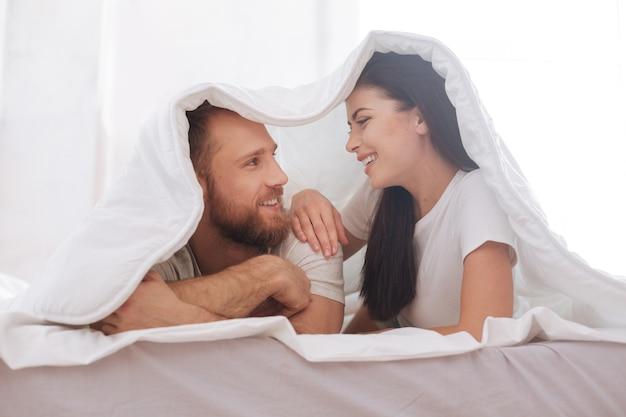 Strahlendes paar, das lächelt, während es auf einem bett unter einer decke liegt und einen augenkontakt aufrechterhält